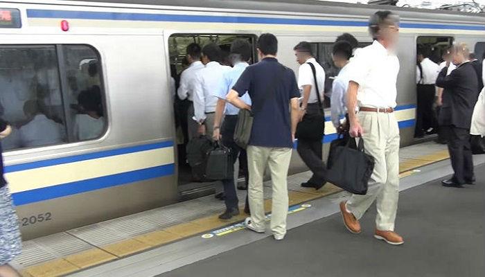 電車で通勤するサラリーマンたち